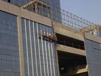 启信大厦 工人在做玻璃外墙装饰
