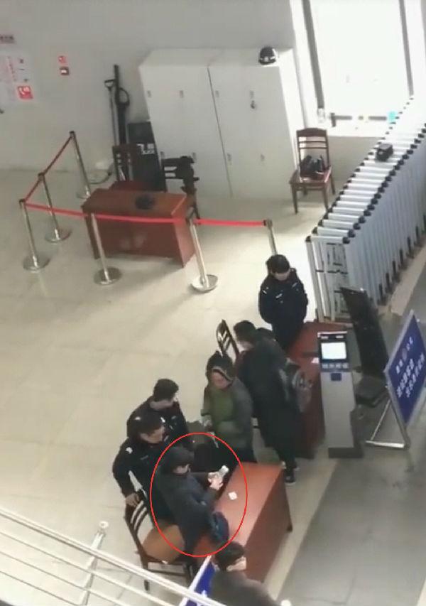 邯郸火车站内便衣女子拍摄旅客身份证。 视频截图
